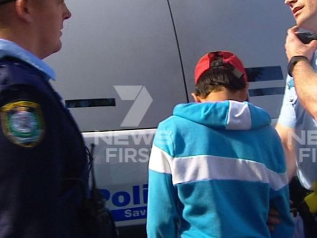 Police lead one of the boys away for questioning. Picture: Channel 7
