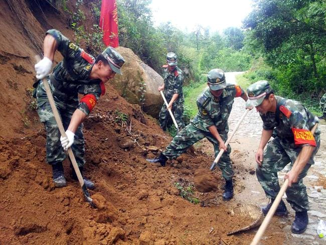 Clean-up effort ... rescuers try to clear off a road at Wupai Villageafter.