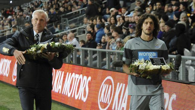 Newcastle manager Alan Pardew, left and captain Fabricio Coloccini carry a wreath of flowers in memory of Newcastle United fans Liam Sweeney and John Alder, who were killed on Malaysia Airlines Flight MH17, before their match with Sydney FC.