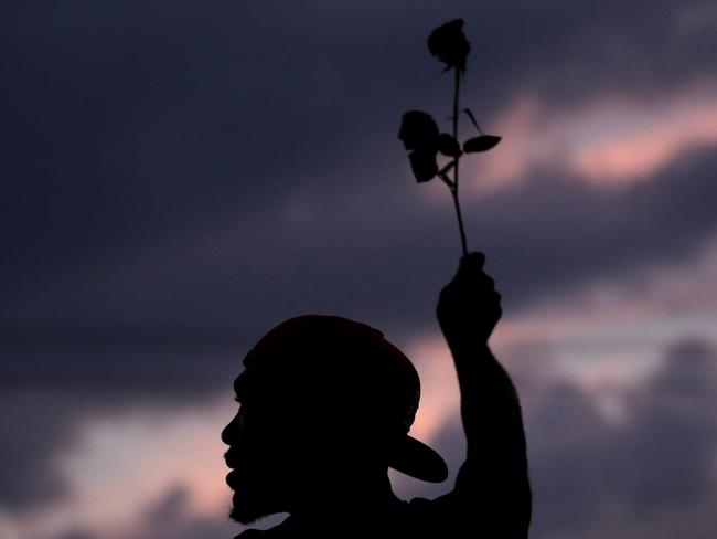 Call for peace ... A man holds up a rose during a protest for Michael Brown who was killed by a police officer in Ferguson.