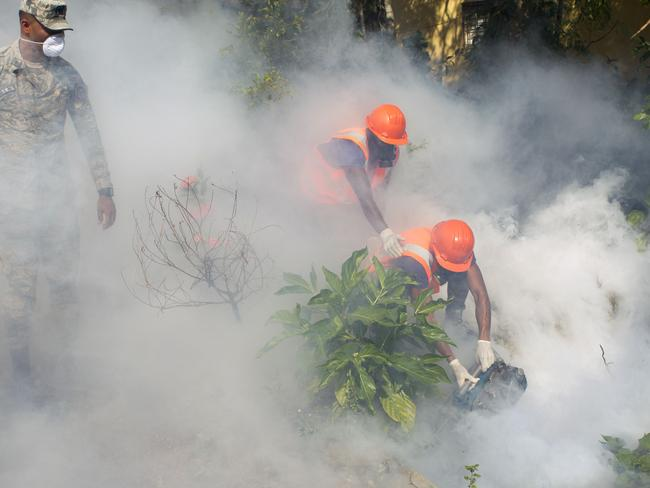 Taking action ... Dominican air force personnel fumigate various locations in Santo Domingo against the Aedes aegypti mosquito, vector of the Zika virus. Picture: AFP/Erika Santelices
