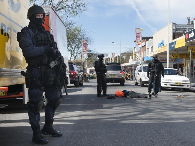 Police stand guard over arrested man.