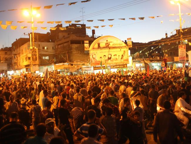 Halt to violence ... Palestinians gather in the streets to celebrate after a deal had been reached between Hamas and Israel over a long-term end to seven weeks of fighting in the Gaza Strip. Picture: Said Khatib