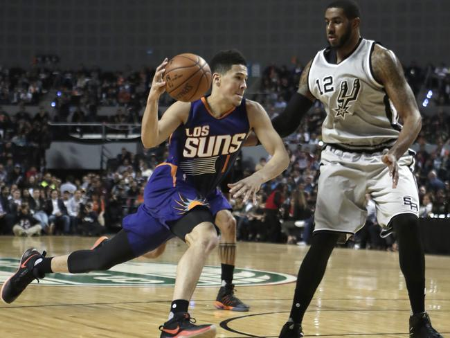 Phoenix Suns Devin Booker, left, drives the ball.