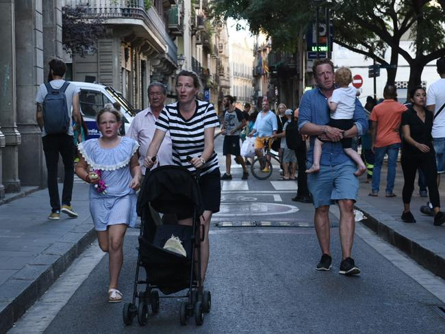 People flee the scene in Barcelona, Spain, after a white van jumped the sidewalk in the historic Las Ramblas district, crashing into a summer crowd. Picture: AP