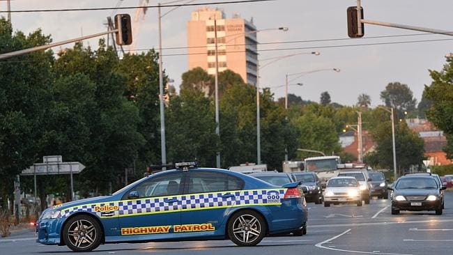 Police stop traffic as the East West Link protesters walk down Alexandra Pde, Fitzroy to another drill site in Clifton Hill. Picture: Nicole Garmston
