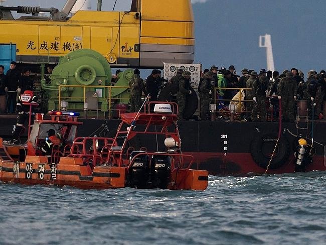 Recovery ... rescue workers assembled on a platform at the spot where the Sewol ferry san