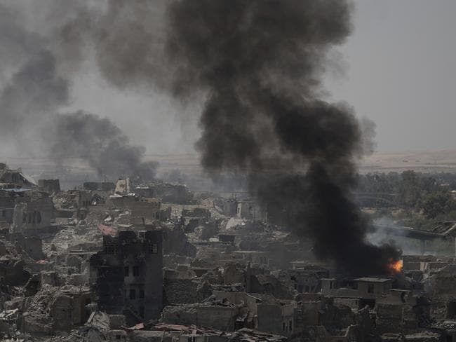 "Smoke billows from Islamic State positions on the edge of the Old City a day after Iraq's prime minister declared ""total victory"" in Mosul. Picture: Photo/Felipe Dana."
