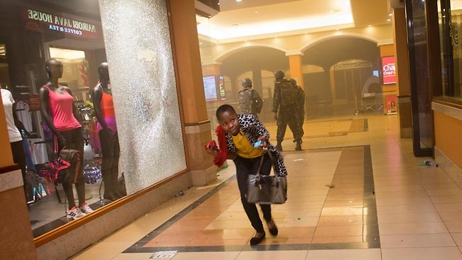 A woman who had been hiding during the gun battle runs for cover after armed police, seen behind, enter the Westgate Mall in Nairobi, Kenya. Picture: AP Photo/Jonathan Kalan