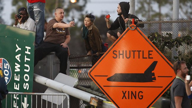People gather near a shuttle crossing sign and a freeway sign that was taken down to make room as the space shuttle Endeavour is transported to the California Science Center in Exposition Park from Los Angeles International Airport. Picture: David McNew