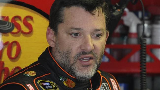 Tony Stewart stands in the garage during practice for a NASCAR Sprint Cup series auto race at Darlington Speedway in Darlington, S.C.