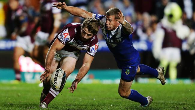 Manly's Kieran Foran is tackled by Bulldogs Trent Hodkinson.