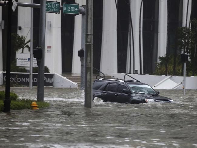 A vehicle drives on flooded Brickell Avenue in Miami. Picture: AP