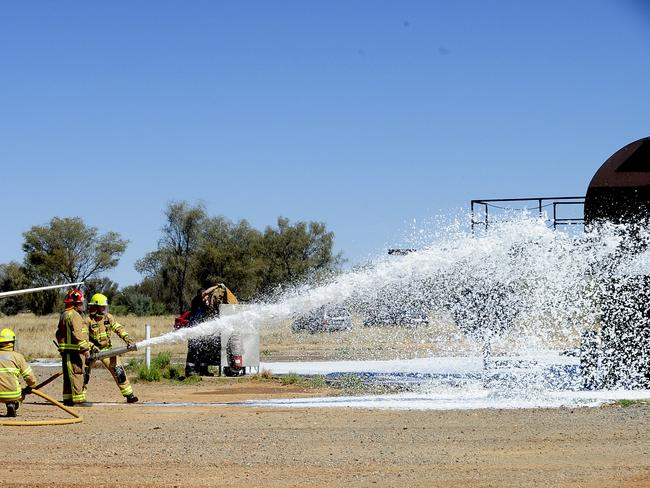 Firefighters conduct a fire drill using foam to quell the flames. Picture: Phil Williams