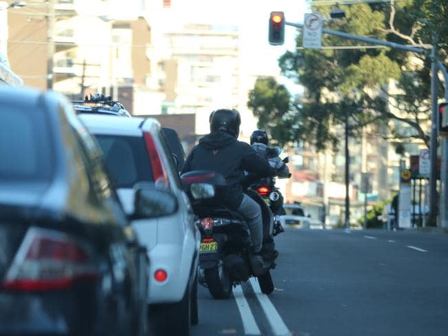 On the move ... A motorcyclist crosses a double unbroken line to overtake stationary traffic. Picture: John Grainger