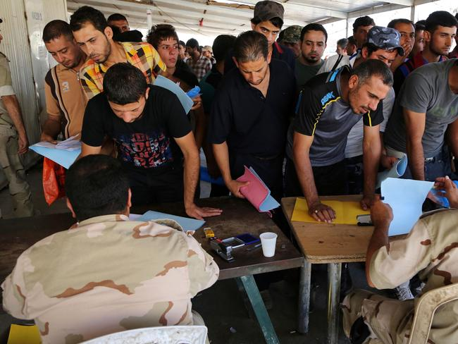 Fightback ... Iraqi men check in at the main army recruiting centre as they volunteer for military services in Baghdad. Picture: Karim Kadim