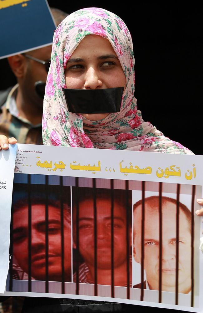 Public protest ... A woman holds a placard during a protest in solidarity with Al-Jazeera journalists (seen on the posters) jailed in Egypt.
