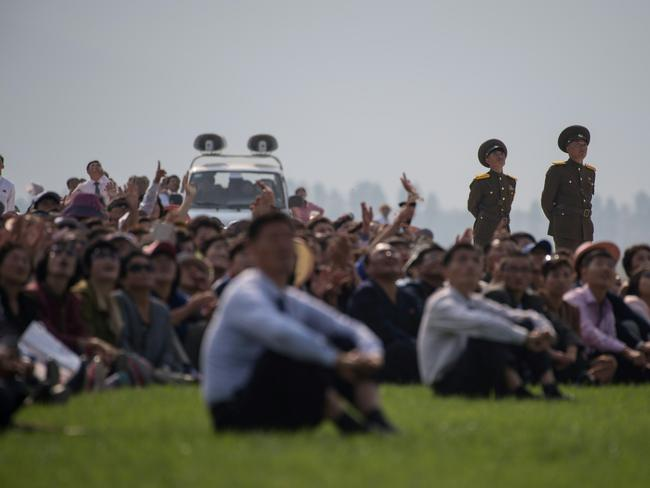 Spectators watch as parachutists perform an aerial display during the second day of the Wonsan Friendship Air Festival in Wonsan last year. Picture: AFP PHOTO / Ed Jones