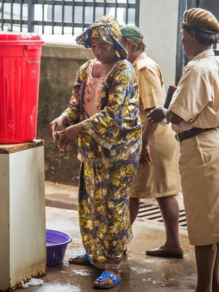 A woman washes her hands in chlorinated water at the Connaught Hospital, which has suffered the loss of medical workers from the Ebola virus, in Freetown, Sierra Leone.