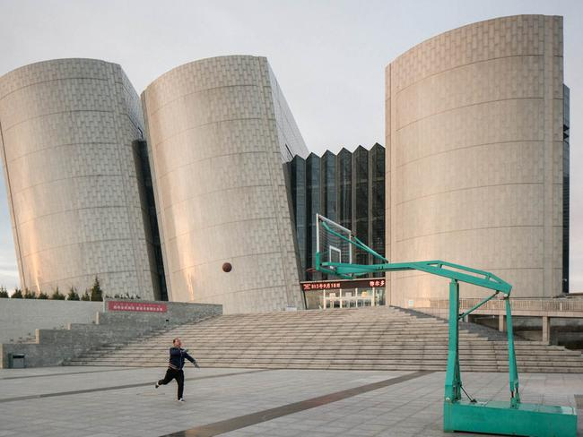 A man plays basketball outside Ordos Library. Picture: Raphael Olivier