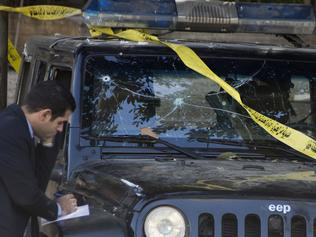 An Egyptian explosives expert takes note of a damage to a police vehicle following a bomb explosion in Cairo, Egypt, Friday, Dec. 9, 2016. Egypt's state-run news agency says the explosion has killed several police and wounded others. MENA says the explosion took place early Friday on Pyramids road, the main avenue leading from the city center out to the Giza pyramids. It says the blast targeted security forces, without elaborating on what caused the explosion. (AP Photo/Amr Nabil)