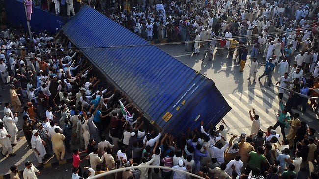 Pakistani Muslim demonstrators topple a freight container, placed by police to block a street during a protest against an anti-Islam film in Lahore. AFP PHOTO / ARIF ALI