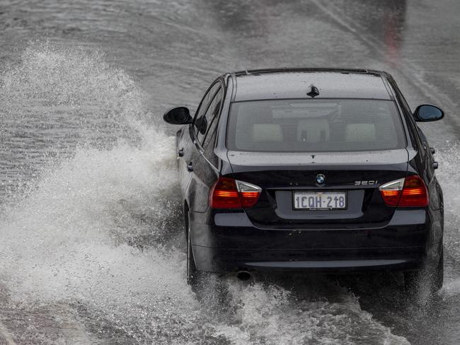 A car battles the rain and wet roads in Perth yesterday. Picture: Matthew Poon