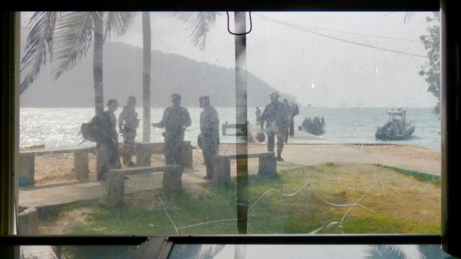 Watching soldiers from inside the beach's duty-free shop.  <i>Picture: Sally Watson</i>