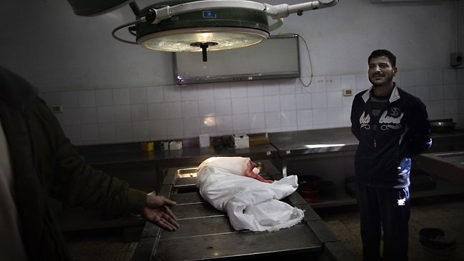 Palestinian Khaled Tafish stands near the body of his 10-month-old daughter Hanen at a morgue in Gaza City on Friday. The baby was killed the day before following an Israeli air strike in the Zeitun neighbourhood. Picture: Marco Longari