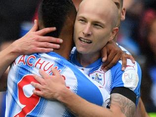 Huddersfield Town's Australian midfielder Aaron Mooy (2L) celebrates scoring the team's first goal during the English Premier League football match between Huddersfield Town and Newcastle United at the John Smith's stadium in Huddersfield, northern England on August 20, 2017. / AFP PHOTO / Anthony DEVLIN / RESTRICTED TO EDITORIAL USE. No use with unauthorized audio, video, data, fixture lists, club/league logos or 'live' services. Online in-match use limited to 75 images, no video emulation. No use in betting, games or single club/league/player publications. /