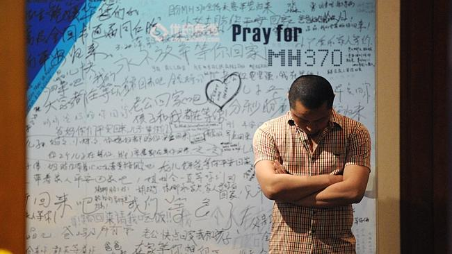 Still praying... A man stands in front of a billboard in support of missing passengers.