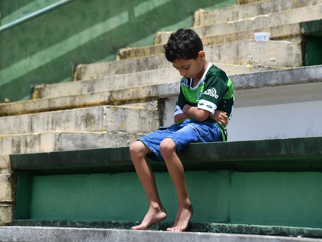 A boy sits alone on the stands during a tribute to the players of Brazilian team Chapecoense Real who were killed in a plane accident in the Colombian mountains, at the club's Arena Conda stadium in Chapeco, in the southern Brazilian state of Santa Catarina. Picture: AFP