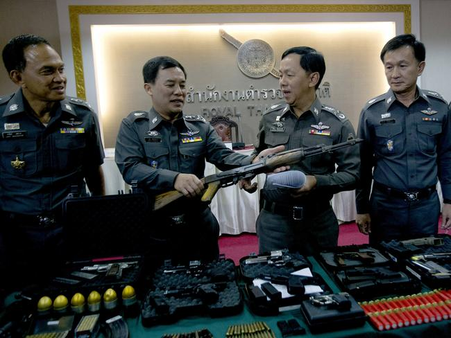 Thai police officers examine war weapons they seized from a raid.