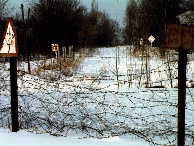Barbed wire & signs warning of danger inside the forbidden zone, a road to Chernobyl lined with abandoned villages in 1996.