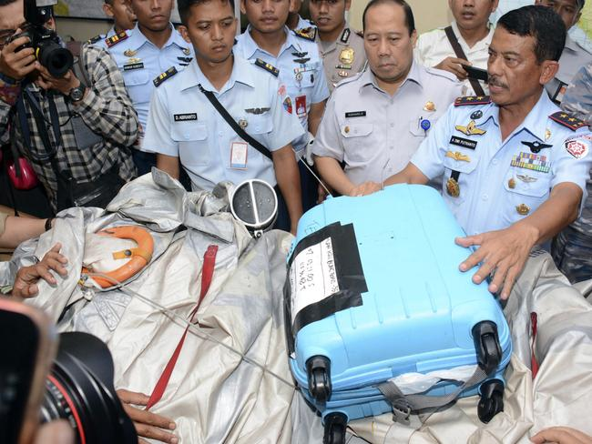 Commander of 1st Indonesian air force Operational Command Rear Marshall Dwi Putranto shows aeroplane parts and a suitcase found floating on the water near the site where AirAsia Flight 8501 disappeared. Picture: Dewi Nurcahyani