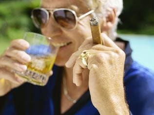 Middle aged adult man holding a glass of whiskey alcoholic drink and a smoking cigar.