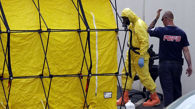 A firefighter dressed in a protective suit walks out of a government mail screening facility