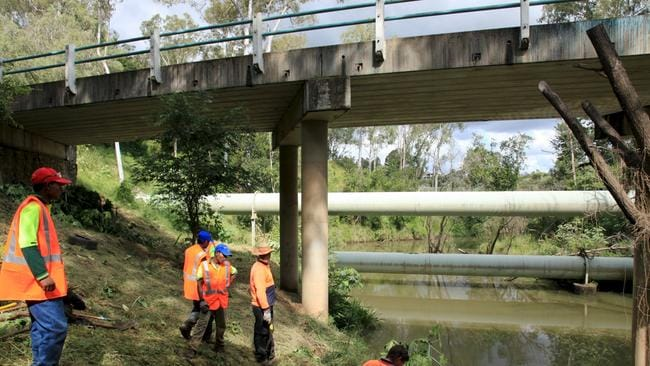 Council workers clear the scrub around Kholo Creek bridge so police divers can search the area where Allison Baden-Clay's body was found. Photographer: Liam Kidston.