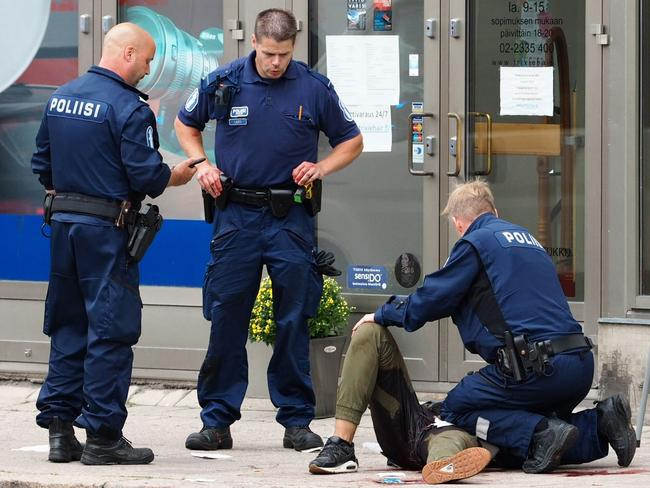 Police officers stand next to a person lying on the pavement in the Finnish city of Turku where several people were stabbed. Picture: AFP