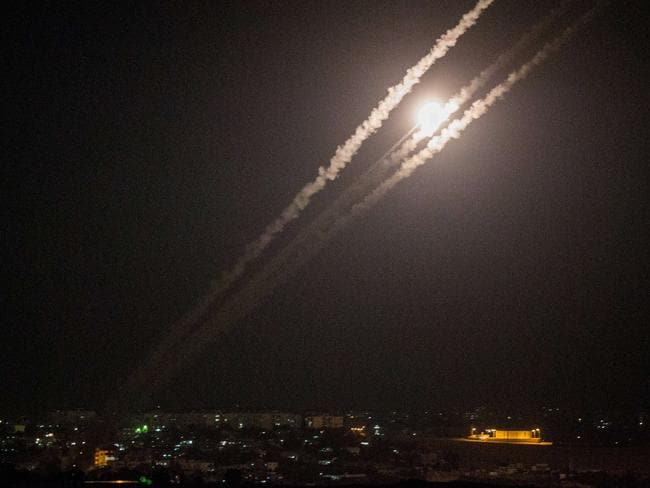 Odd, angry shot ... This picture taken from the southern Israeli Gaza border shows rockets being fired from the Gaza strip into Israel.