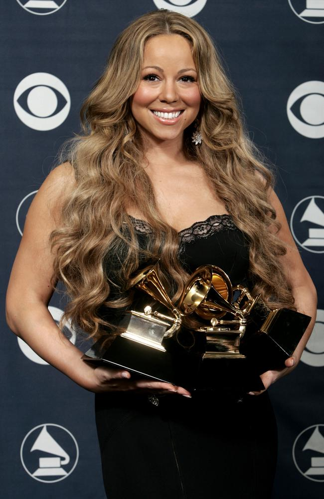 Mariah Carey holds her three Grammys for best female R&B vocal performance, best contemporary R&B album, and best R&B song at the 48th Annual Grammy Awards in 2006.