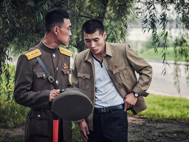 Regime soldiers, who maintain a presence everywhere in North Korea, chat without realising they are being photographed. Picture: Michal Huniewicz /Exclusivepix Media