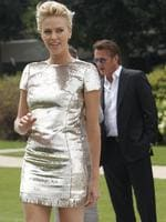 Actress Charlize Theron poses while actor Sean Penn, right behind, talks as they arrive at the Christian Dior show as part of Paris Fashion Week - Haute Couture Fall/Winter 2014 in Paris, France. Picture: AP