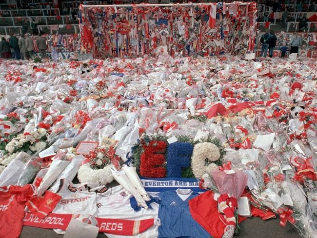 FILE - In this April 17, 1989 file photo, floral tributes are placed by soccer fans at the 'Kop' end of Anfield Stadium in Liverpool, England, 2 days after the Hillsborough April 15 tragedy when fans surged forward during the cup semifinal between Liverpool and Nottingham Forest at Hillsborough Stadium killing 96 people. British prosecutors on Wednesday June 28, 2017, are set to announce whether they plan to lay charges in the deaths of 96 people in the Hillsborough stadium crush _ one of Britain's worst-ever sporting disasters. (AP Photo/ Peter Kemp, file)