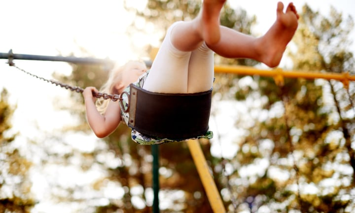 Shot of a happy little girl swinging in the park