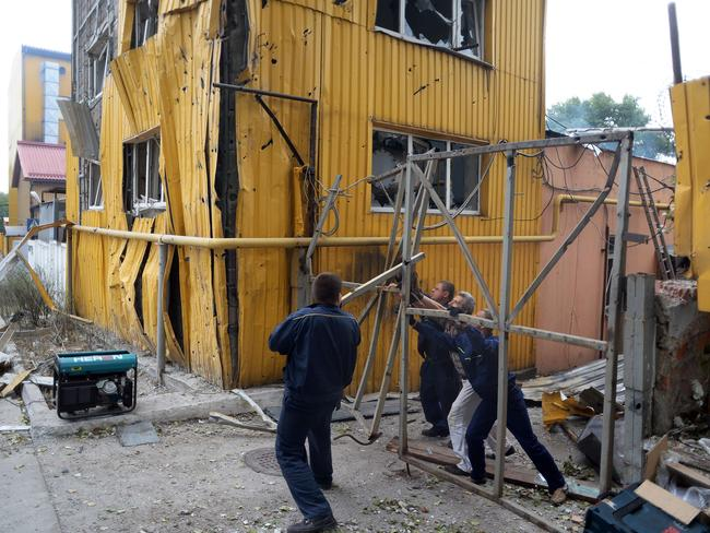 Invaded ... workers try to repair the gate of a bakery damaged during a shelling in the Kievski neighbourhood in northern Donetsk on August 28, 2014.