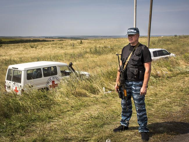 A member of a local militia stands guard as vehicles transporting observers from the Organisation for Security and Co-operation in Europe and International Committee of the Red Cross visit the main crash site of Malaysia Airlines flight MH17 in Grabovo, Ukraine. Picture: Rob Stothard/Getty Images