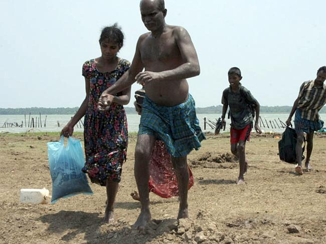 In flight ... a file photo from 2009 shows civilians who managed to escape from the last remaining Tamil rebel-held patch of coastline in the northeastern district of Mullaittivu. Many asylum seekers claim persecution over the separatist conflict.