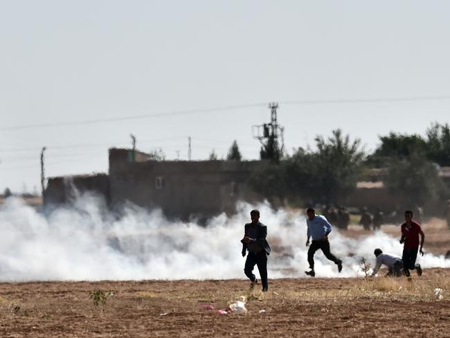 Under siege ... Kurds run from tear gas in the village of Mursitpinar next to the Syrian town of Ain al-Arab on the Turkish-Syrian border. Picture: AFP