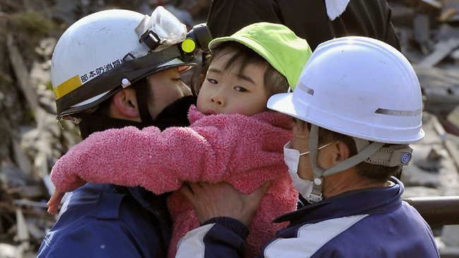 Recovery continues ... a child is held by rescue workers after being rescued from a building at Kesennuma, northeastern Japan, on Saturday March 12, 2011, one day after a giant quake and tsunami struck the country's northeastern coast.